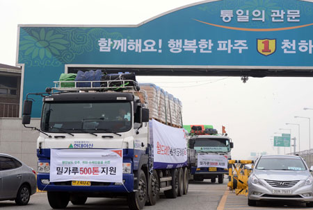 Trucks loaded with flour as relief aid to North Korea pass a checkpoint on a bridge over the Imjin River in the South Korean border city of Paju, Gyeonggi Province, in this Sept. 21, 2012, file photo. The Seoul government sent 500 tons of flour to the impoverished North in one of the lastest aid supplies under the previous Lee Myung-bak administration. (Photo by Korea Times)