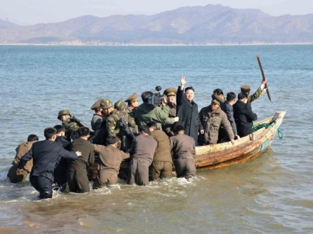 In this March 11, 2013 photo released by the Korean Central News Agency (KCNA) and distributed March 12, 2013 by the Korea News Service, North Korean leader Kim Jong Un waves at military officers after inspecting the Wolnae Islet Defense Detachment, North Korea, near the western sea border with South Korea.
