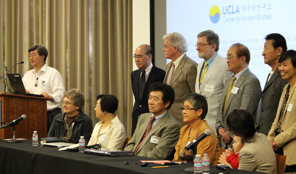Podium and first row, left to right: Paul Liem, Korea Policy Institute; Dorothy Ogle, former Methodist missionary to South Korea; Pilju Kim Joo, Agglobe Services International; Indong Oh, M.D.; Jeong Young-Hee, farmer and peace activist from Gangjeong, Jeju Island; Christine Ahn (back turned), Global Fund for Women and Oakland Institute, and daughter. Top row, left to right: Moon Jae Pak, M.D., U.S.-North Korea Medical Science Exchange Committee; historian Bruce Cumings, University of Chicago; Erich Weingartener, CanKor; Rev. Syngman Rhee; James Chun, One Korea Movement; Hosu Kim, City University of New York. (Photo by Peggy McInerny)