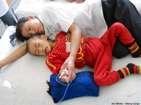 A North Korean mother lies with her acutely malnourished son, plagued by sores, at a county hospital in September 2011. (Photo by Jim White, Mercy Corps)